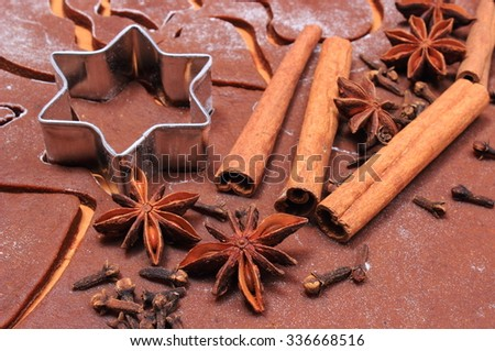 Spice for baking, anise cinnamon sticks and cloves, cookie cutters on dough for Christmas cookies and gingerbread, concept of baking and Christmas time - stock photo