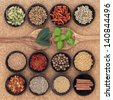 Spice, herb and food ingredient sampler in wooden spoons and bowls over cork background. - stock photo