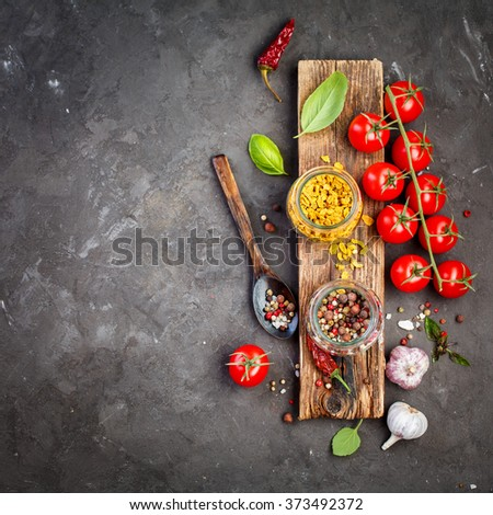 Spice mix and ingredients for cooking,  basil, garlic, pepper and cherry tomatoes. Black background, copy space