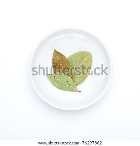 Spice series: Laurel leafs The bay laurel is an aromatic evergreen tree or large shrub native to the Mediterranean region. Seen from directly above, on a small porcelain plate. - stock photo