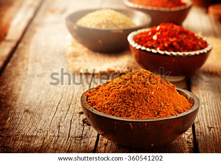 Spice. Various Spices over Wooden Background. Saffron, turmeric, curry in bowls on wooden table - stock photo