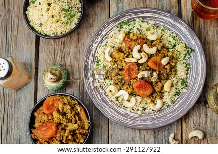 Spiced mince with dried apricots, cashew nuts and couscous. Moroccan dish. the toning. selective focus - stock photo