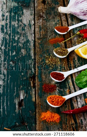 Spices and herbs assortment on spoons over wooden background. Vegetarian food, health or cooking concept. Selective focus. - stock photo
