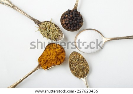 Spices and herbs in silver spoons - stock photo