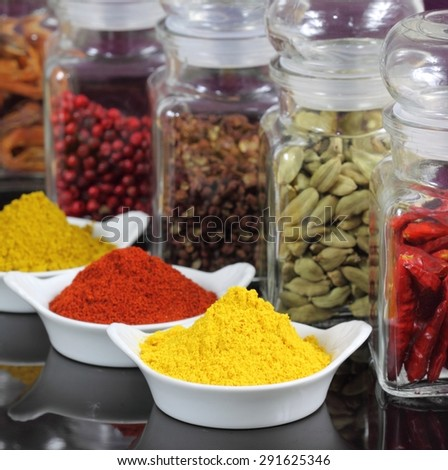 Spices and herbs in white ceramic bowls and glass jars. Food and cuisine ingredients. - stock photo