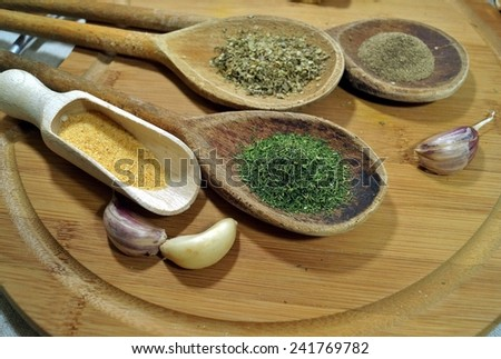 Spices and herbs on wooden spoons - stock photo