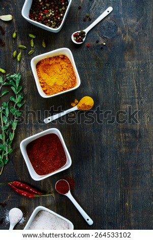 Spices and herbs selection on dark wooden background. Food and cuisine ingredients. - stock photo