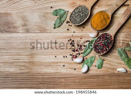 Spices and herbs. Spice greens in spoons on wooden background. Curry, turmeric, basil, pepper and other over wooden background. - stock photo