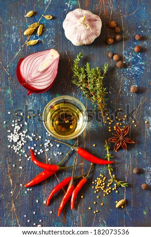 Spices and herbs with aromatic olive oil on an old wooden board. Rustic style. - stock photo