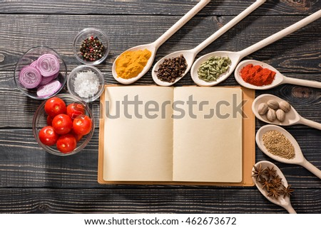 spices and open book of recipes on a dark wooden background, top view