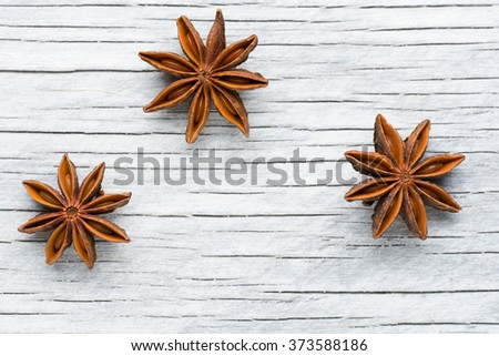Spices. Anise stars on the vintage wooden background. - stock photo