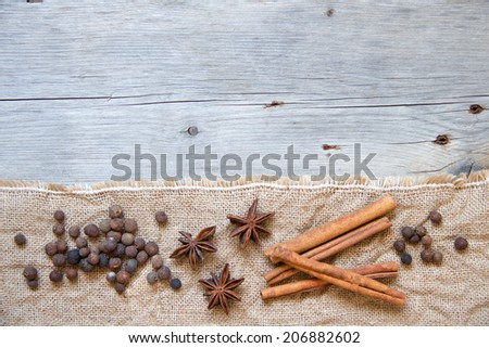 Spices background - cinnamon, pepper and anice on burlap and wood