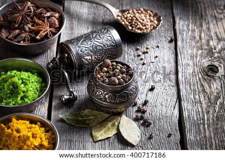 Spices, bronze pepper grinder and spoon with cumin seeds at wooden green background - stock photo