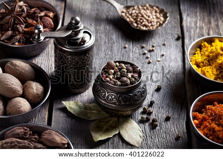 Spices, bronze pepper grinder and spoon with cumin seeds at wooden green background