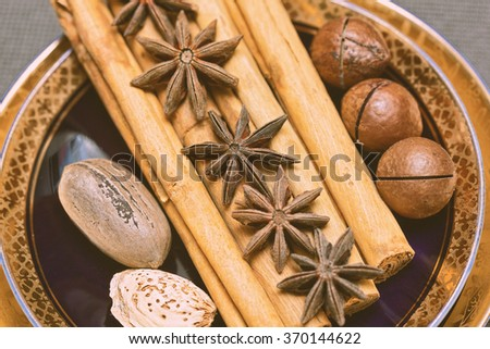 spices cinnamon and star anise, pecans, macadamia nuts and almonds on a saucer in vintage style. Christmas ingredients - stock photo