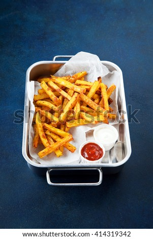 Spices curry fried potatoes in a metal baking dish, selective focus - stock photo