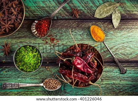 Spices, dry red chili peppers at wooden green background with spoons nearby