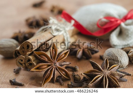 Spices for mulled wine. Closeup of cinnamon sticks, anise stars and cloves on wooden background. Selective focus. Macro with shallow dof.