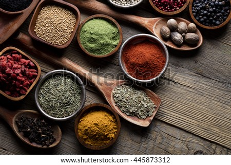 Spices. Herbs and spices selection in old metal and wooden bowls over wooden background. Rosemary, ginger and chili pepper.