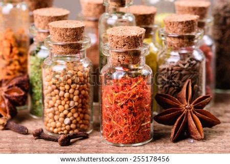 Spices in bottles on wooden background - stock photo