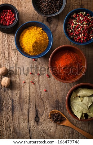 spices in bowls: pink and black pepper, paprika powder, curry, bay leaf - stock photo