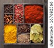 spices in box: pink and black pepper, paprika powder, curry, bay leaf; anise; clove; cumin - stock photo