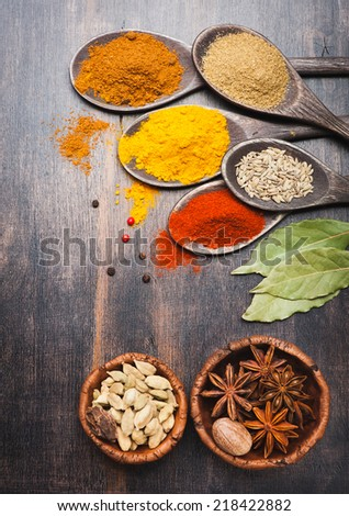 Spices in wooden spoons on a wooden board. Food and cuisine ingredients.  - stock photo