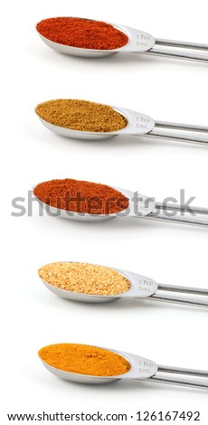 Spices measured in metal teaspoons, isolated on a white background: chilli powder, curry powder, cayenne, garlic granules and turmeric. - stock photo