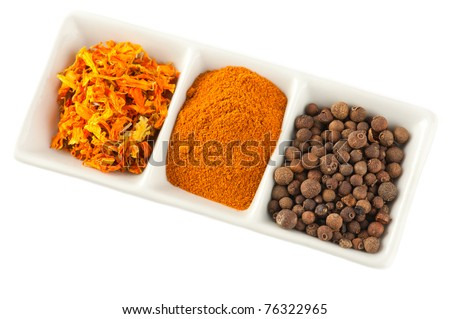 Spices. Mix of different dry herbs: pepper balls, saffron and chili on plate isolated on white background - stock photo