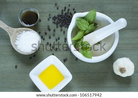 spices on table, basil in mortar, wooden background, top view - stock photo