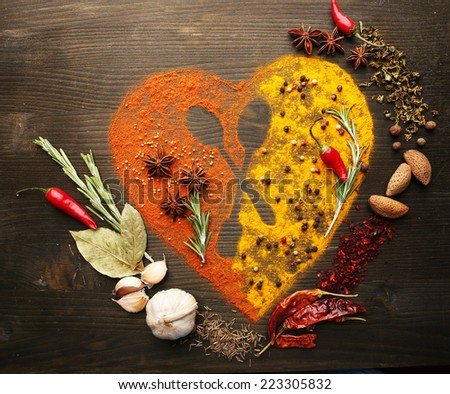 Spices on table in shape of heart with spoon silhouette, close-up  - stock photo