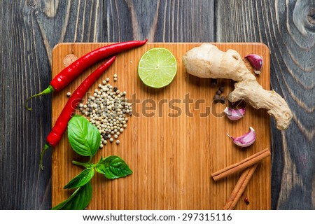 Spices over wooden background with empty place for text. Chilli pepper, garlic, pepper corns, basil and ginger. - stock photo