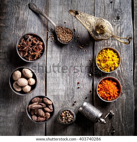Spices, pepper grinder, Aladdin lamp, spoon with seeds at grey wooden background  - stock photo