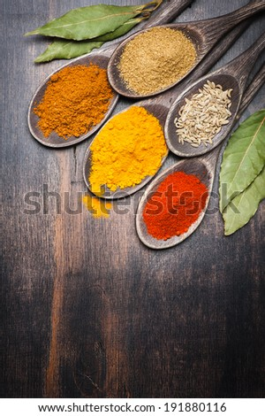 Spices. Spice on dark background. Curry, chili, coriander, bay leaf. - stock photo