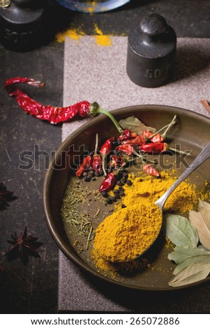 Spices turmeric and dry red hot chili peppers on metal plate, served over dark table with vintage weight and blue ceramic plate. - stock photo