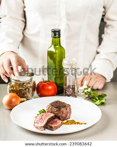 spices, vegetables and a dish of fried medallion on a background of cooks - stock photo