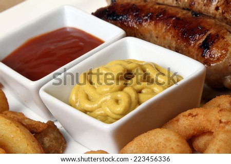 spicy American grilled sausages served on a white plate with two spicy sauces and delicious baked potatoes and crunchy onion rings ketchup  mustard