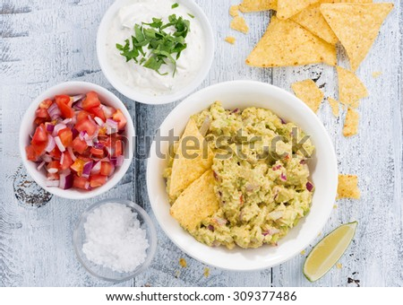 spicy avocado sauce and assorted sauces with corn chips on wooden table, top view, horizontal - stock photo