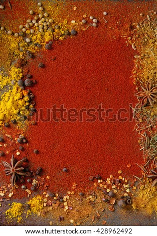Spicy background with assortment of different hot chili and allspice peppers and mix of other spices with red paprika powder as background. Top view. With space for text