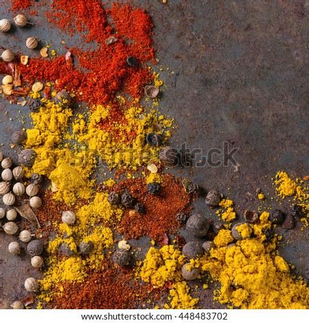 Spicy background with assortment of different hot chili and allspice peppers and mix of other spices over old rusty iron background. Top view. With space for text. Square image - stock photo