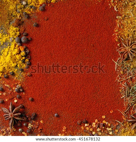 Spicy background with assortment of different hot chili and allspice peppers and mix of other spices with red paprika powder as background. Top view. With space for text. Square image - stock photo