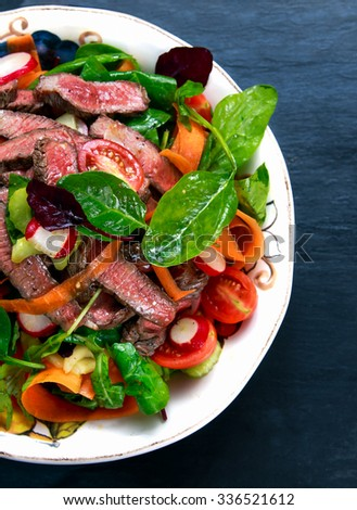 Spicy Beef Slices Meat Salad with Carrots, Tomatoes, Cucumber, Parsley and Salad leaves Spinach, rocket, red ruby chard on old blue stone background. - stock photo