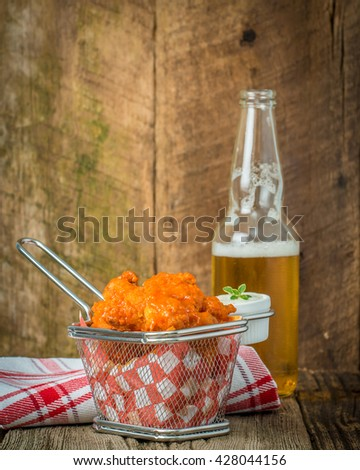Spicy buffalo style chicken wings in a basked served with beer. - stock photo