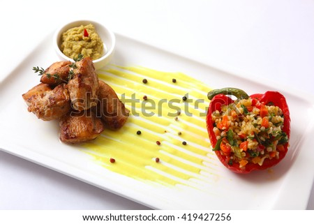 Spicy bulgur with mushrooms and chicken on yellow souce - stock photo