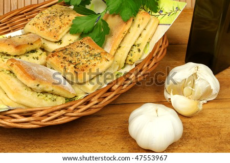 Spicy buns with garlic and parsley in basket, olive oil bottle and fresh garlic on wooden board