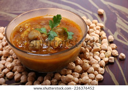 spicy chana masala, raw chickpeas around the bowl indian dish - stock photo