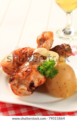 Spicy chicken drumsticks and new potatoes - closeup - stock photo