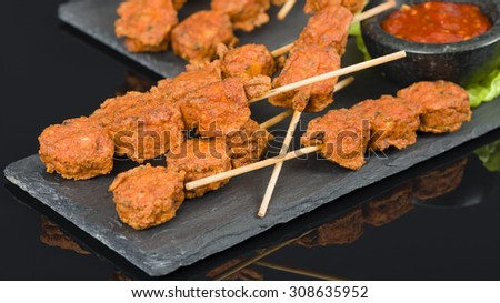 Spicy Chicken Satay - Marinated chicken meatball skewers served with chilli sauce and lemon wedges on a slate with reflections.  - stock photo