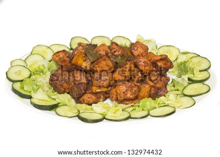 Spicy chicken tikka served in a tray with lettuce - stock photo