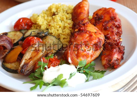 Spicy chicken with couscous and roasted vegetables - stock photo